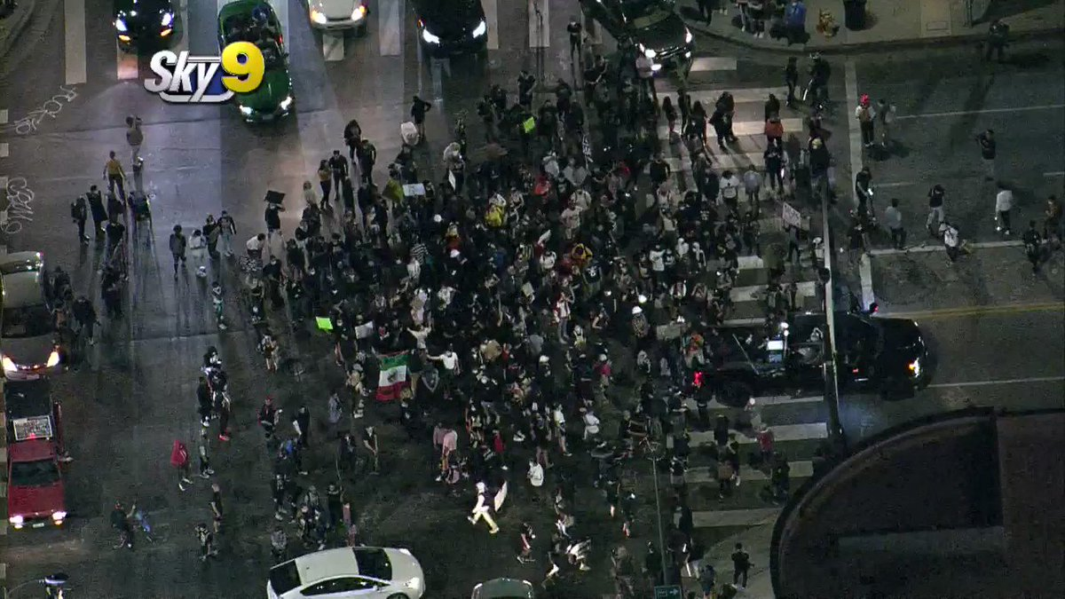 WATCH: A person driving a white Prius was chased down and by protesters after trying to drive through the crowd in #Hollywood. The group that chased the driver began hitting the car and possibly broke a window. @RoadSageLA was overhead in #Sky9 as it happened. #CBSLA