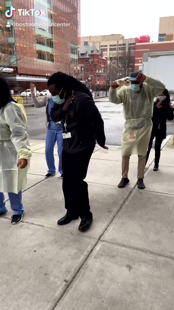 Boston health care workers dancing on the sidewalk to celebrate the arrival of the first  covid-19 vaccine.