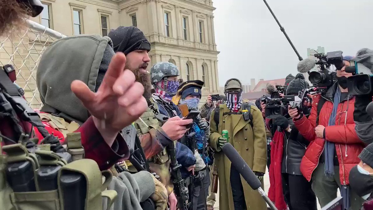 A man who aligns with Boogaloo boys makes a statement in front of Michigan State Capitol.