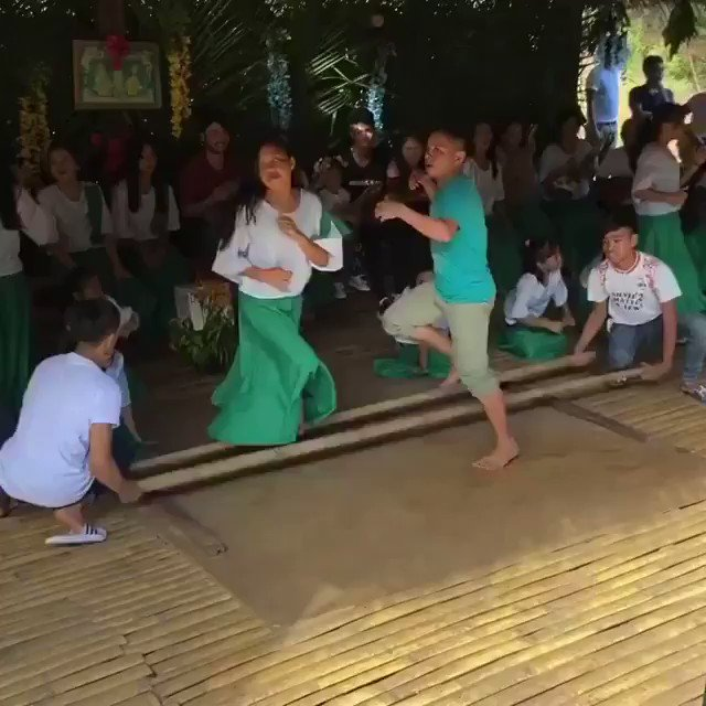 Young dancers in the Philippines performing a traditional bamboo dance known as Tinikling.