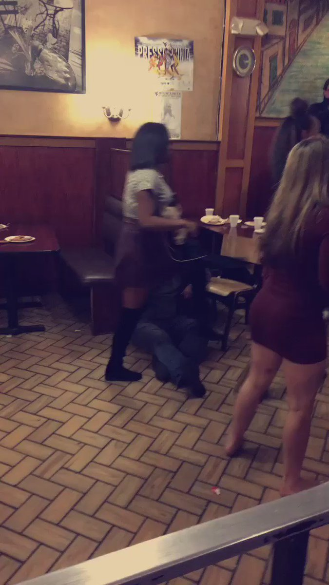 This guy calmly eating pizza during a 20-person restaurant brawl clearly has his priorities straight