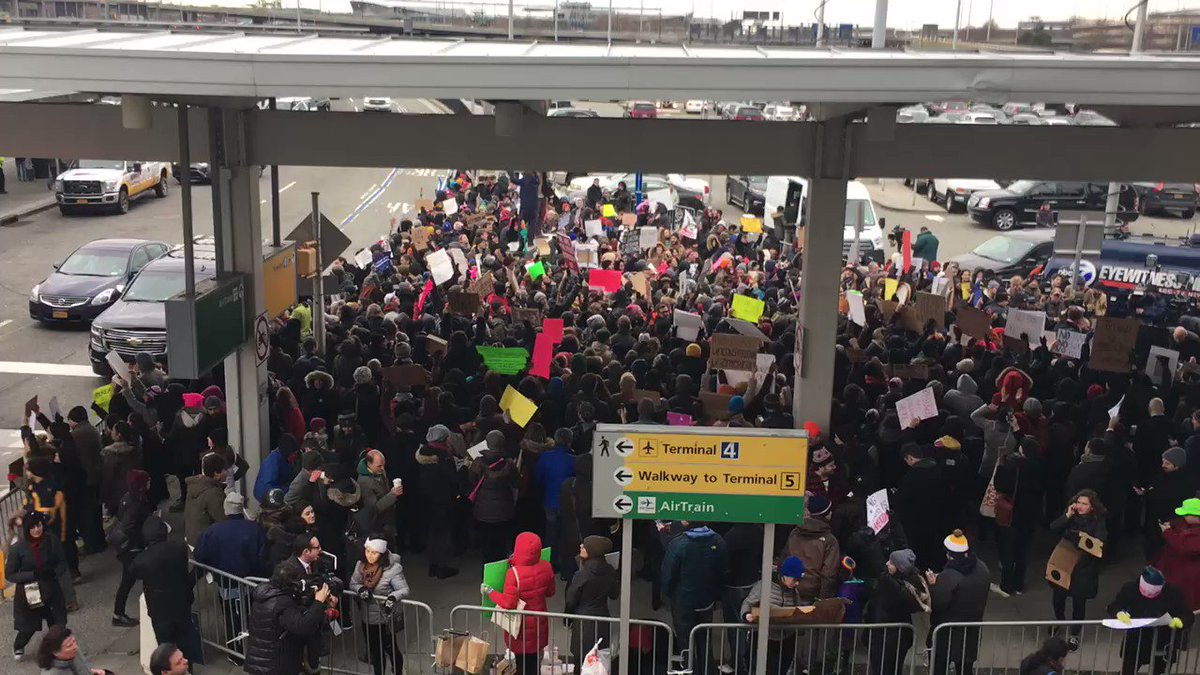 """RIGHT NOW: Crowd chanting """"Let them in! Let them in!"""" at JFK terminal 4 airport. #MuslimBan https://t.co/ZCLFsmUxgm"""
