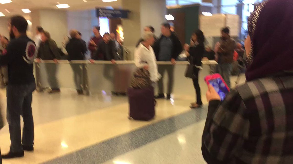 #breaking the 1st woman who was held has been let through. Crowds chant USA as she's reunited with her family. https://t.co/A7s3SIRK11