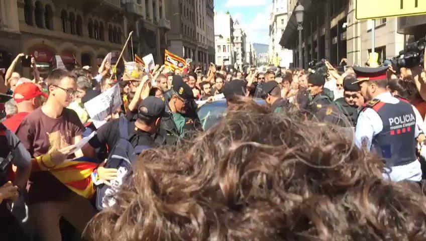 Los manifestantes, sentados en el suelo, para intentar barrer el paso al coche donde iba detenido Xavi Puig, responsable de Exteriores.