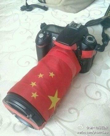 To avoid being attacked, CN reporters have to use flags cover their Canon cameras. pic.twitter.com/NgvyNh3r