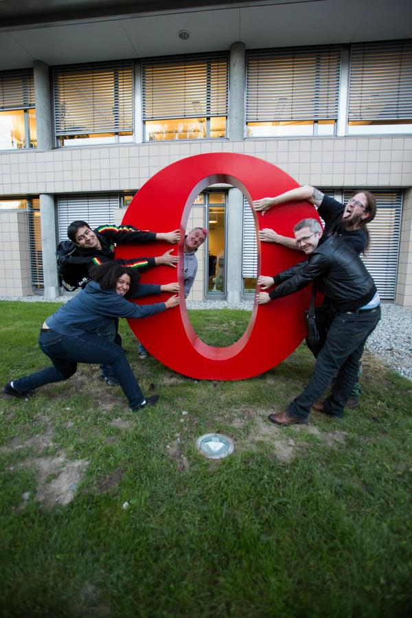 members of Opera's devrel team pull open a large red letter 'O' Opera logo