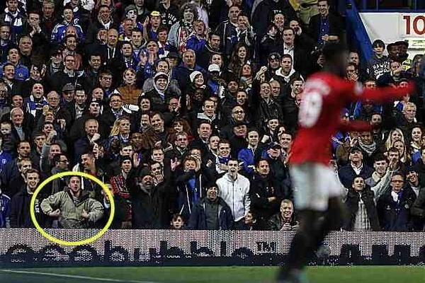 Picture: A racist Chelsea fan is snapped making a monkey gesture towards Manchester Uniteds Danny Welbeck