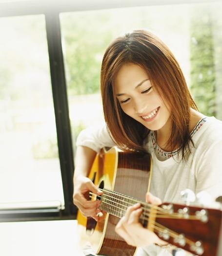 笑顔でギターを弾くYUI