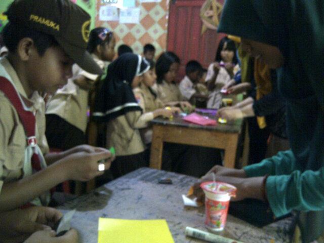 """""""Raffly, begini cara lipat buat boxnya"""", kata Ifa, relawan NBS sembari memainkan tangan melipat kertas"""