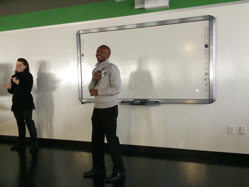 Juwan enthusiastically presenting, ASL interpreter in background