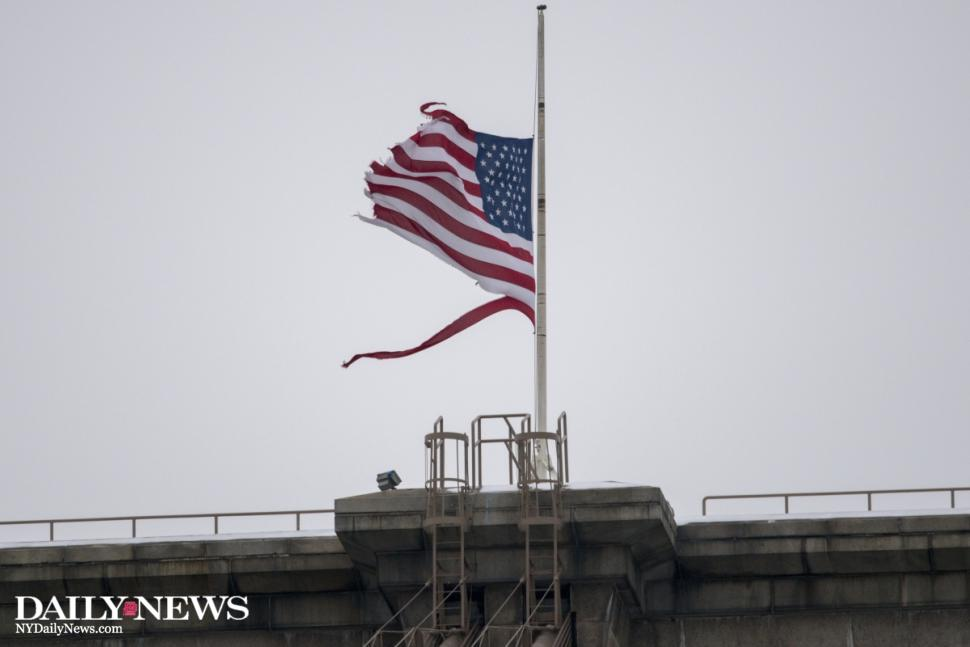 Image of a torn and battered American flag on top of the Brooklyn Bridge.
