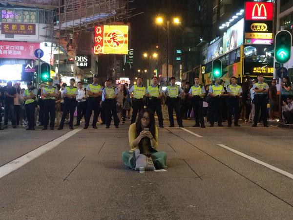 Lady sitting in front of #Police defense line  in #OccupyMongkok 世界將我包圍 #Occupycental #HK http://t.co/5NdkpiDnsq