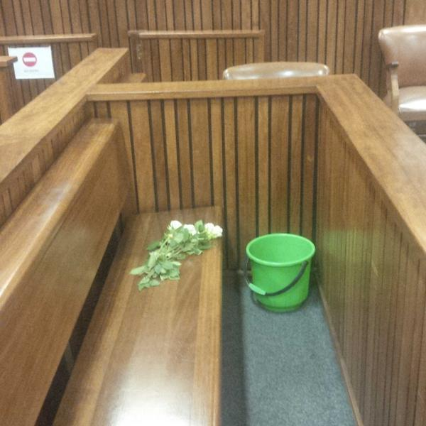 This is all that remains in the Oscar Pistorius dock. White roses and a sick bucket (empty). #OscarPistorius http://t.co/xjY3BU5eQp