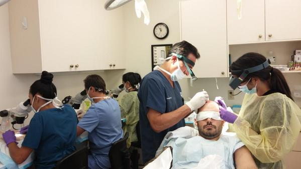 Dr. Mejia is creating more hair sites while his assistant is placing hair follicles. #Hairtransplant http://t.co/0FsYUMBM2r