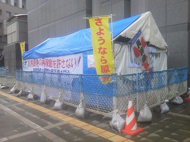 鹿児島の方より、悲しい写真が届きました。鹿児島県庁前に市民グループが設置したテント、今朝の時点でもう行政がフェンスをめぐらしたと。 #川内原発 地元のグループがずっと求めてきたのは、「公開討論会」や「公聴会」を開くこと。これが答え? http://t.co/xJUOrkE7oh