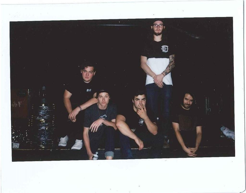 The State Champs guys are posing in a Polaroid photo onstage in front of their instruments.
