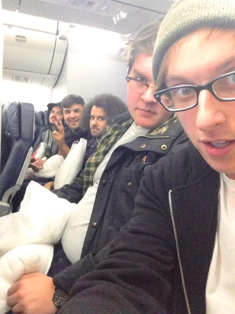 A State Champs selfie while they are sitting on an airplane that is flying to the UK. Derek and Tyler are wearing glasses. They are holding pillows.