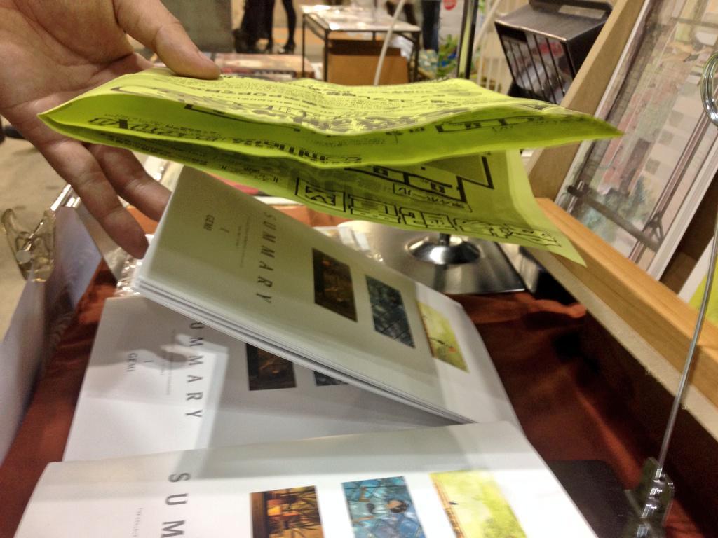 【拡散希望】本日コミティアにて本を万引きされました。手口は写真のような感じです。チラシで手元を隠しながら指で本を掴むようにしていました。空いた方の手でポストカードを見るふりをしていたので慣れてる人でしょう。皆様もお気をつけください!