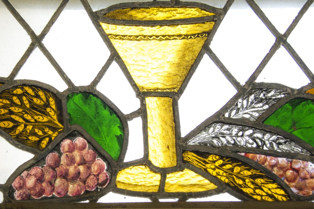stained glass depicting a cup, grapes, and grain
