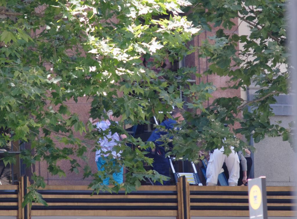 People evacuating via small ladders (above the Lindt cafe) #sydneysiege #MartinPlaceSiege Photo by@John__Donegan http://t.co/G8HhZwnR9h