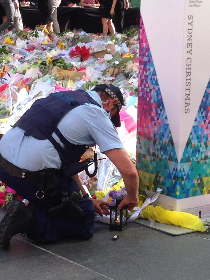 A policeman tends a candle at the Martin Place memorial. http://t.co/ywow4BIlaS