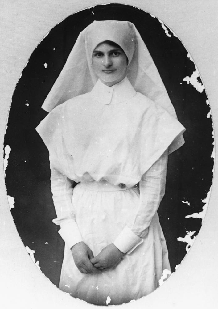 1922年頃、オーストラリア、クイーンズランド州、看護師の女性の写真。クイーンズランド州立図書館所蔵。ナースキャップは修道女のベールがルーツとも言われ、ヴィクトリア朝時代には白いものに変わっていった。