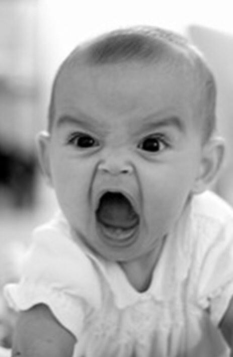 Un bambino piccolissimo con una faccia arrabbiatissima