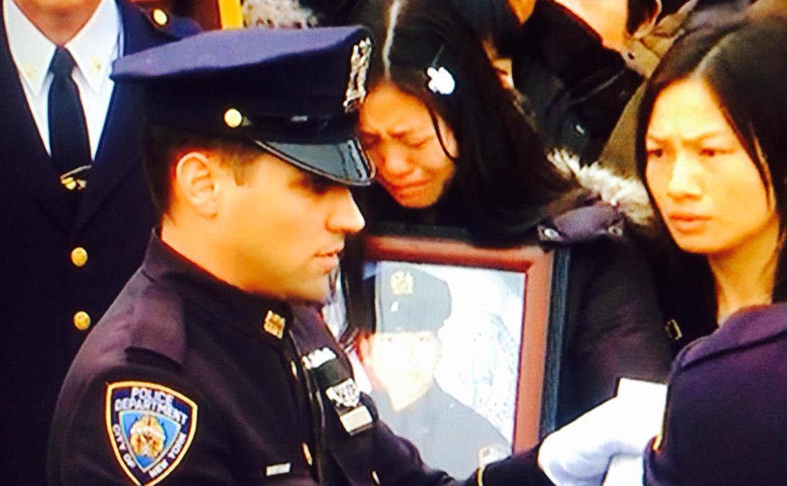 Heartbreaking. Detective Wenjian Liu's widow weeps while clinging to his photograph. http://t.co/sThPWSY1kv