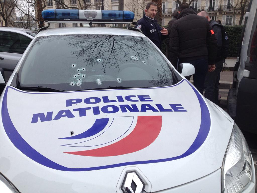Police car with bullet holes in front of Charlie hebdo headquarter. Photo  @WilliamMolinie http://t.co/lzQdhJ6kxR