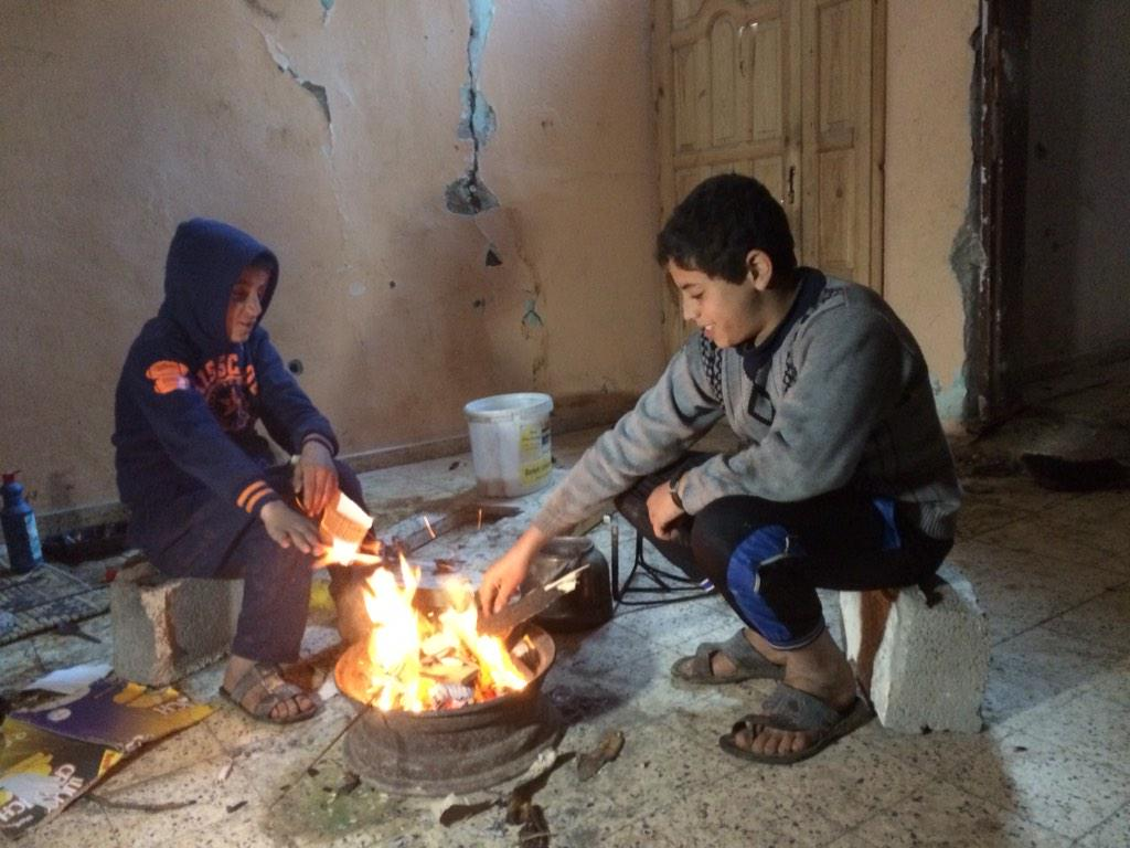 This is how families are trying to keep warm in rain, hail, wind and near freezing temps in Shujaiya. #Gaza http://t.co/w0ZLflSzLV