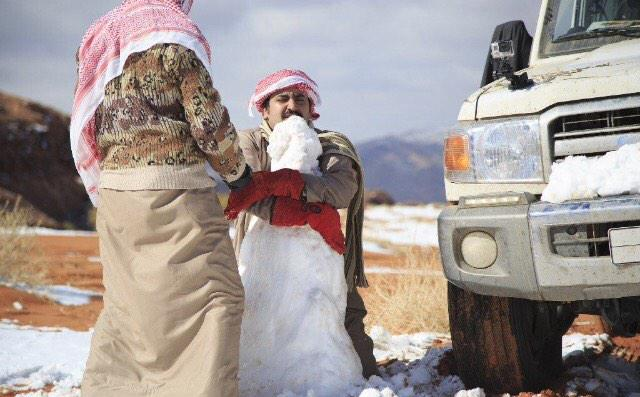 Saudi men make a snowman in the Aleghan Heights, in the Tabuk region