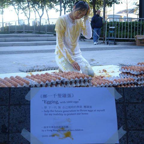 """在立法会外,一名育有两女的母亲以一千只鸡蛋砸向自己,表示""""替下一代对自己现时的无能掷鸡蛋""""。早前香港警察拘捕一名准备向特首梁振英掷蛋的男子,她的行动是为了嘲讽不让人扔鸡蛋的梁振英,也痛心她这一代人无能力保护下一代(香港独立媒体) http://t.co/Q7YNkIhFIa"""