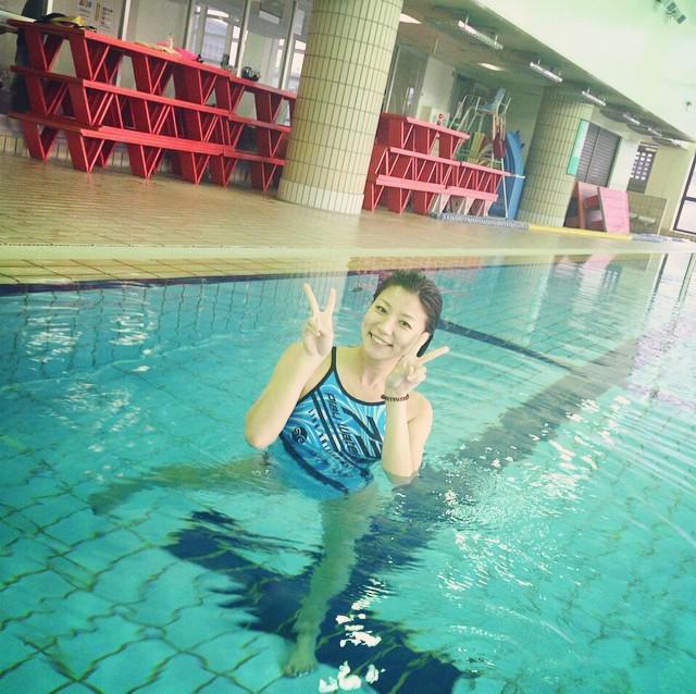 プールの中でピースをしている青木愛