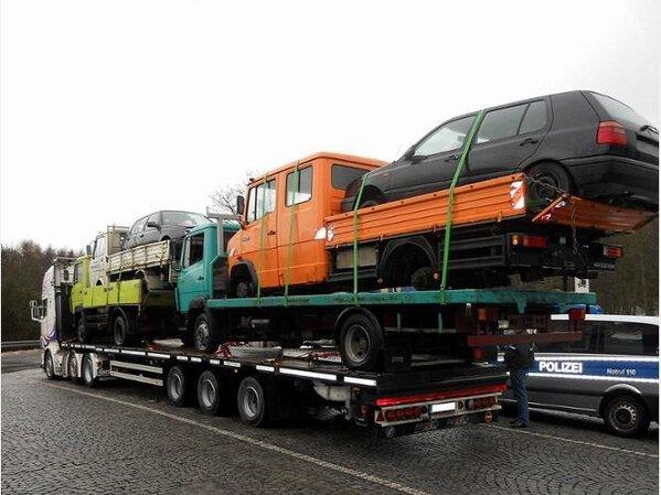 Langer Truck, auf den zwei kurze LKW geladen wurden, die jeweils einen LKW tragen, auf denen jeweils ein PKW steht.