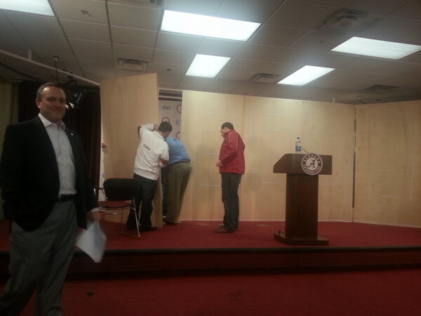 Late, mad scramble to set up Saban's presser. It's like Restaurant Impossible in here. 16 minutes until the man arrives http://pic.twitter.com/Txq4bCCk