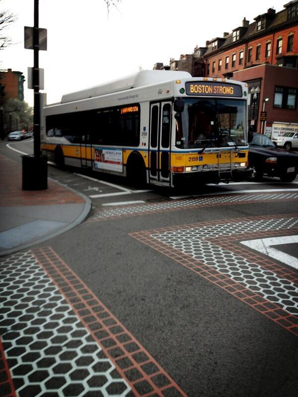 A bus going through South Boston proudly displays 'Boston Strong' on its head sign and side LED sign.