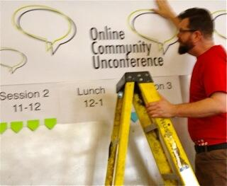Preparations for OCU2013 are complete at the venue. Here's scott hanging a banner above the schedule wall #ocu2013 pic.twitter.com/dvJfZhGmMk