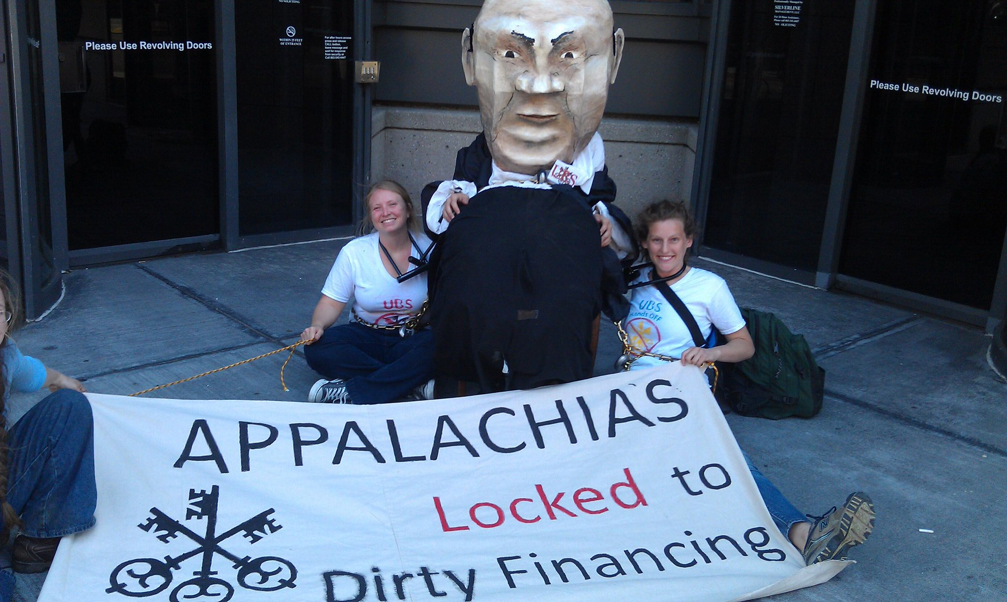 Two women locked to fat cat banker puppet at UBS Knoxville office.