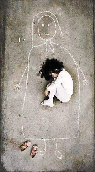 A young Iraqi orphan missing her mother, so she drew her and fell asleep inside her