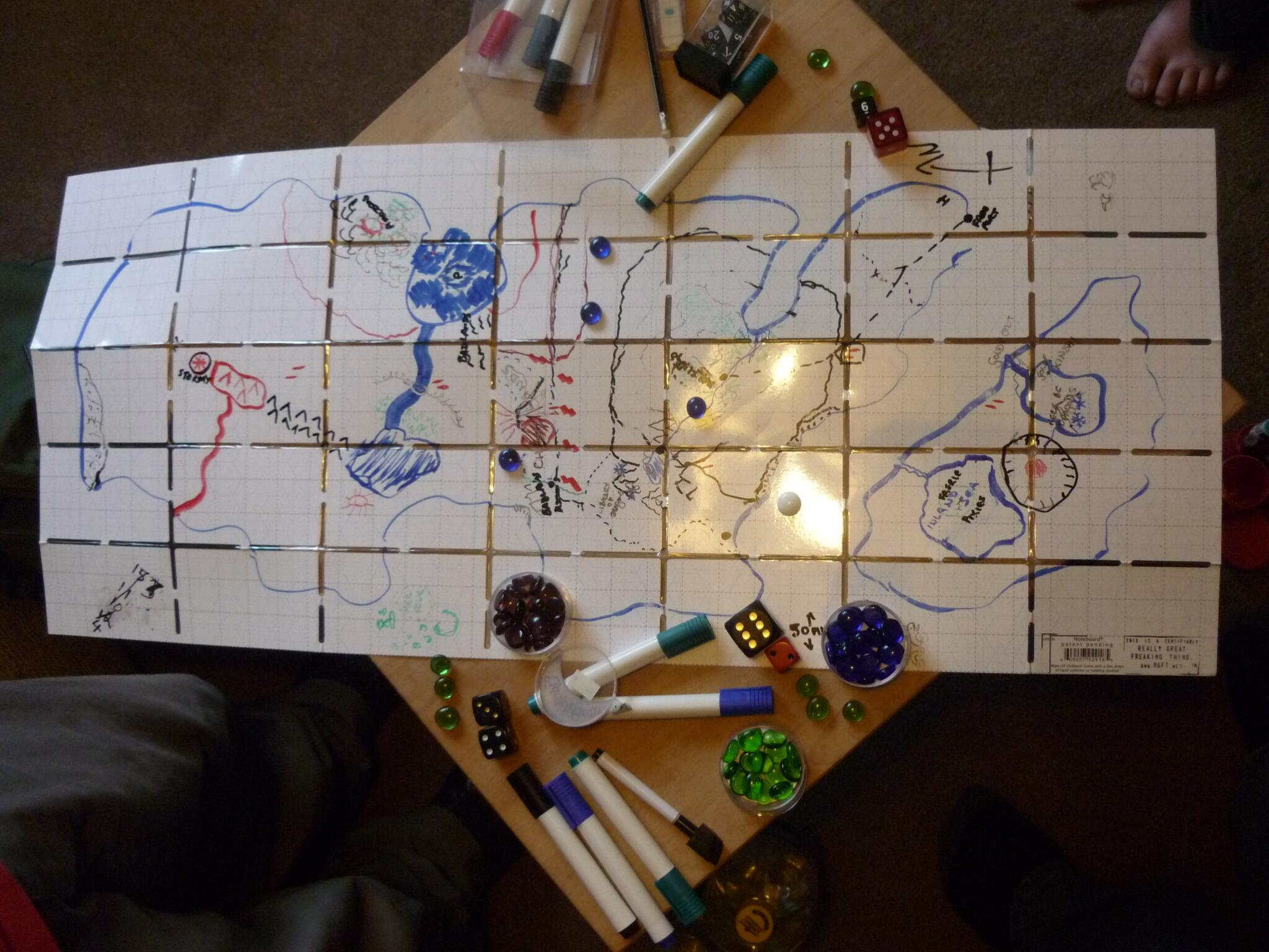 A foldable whiteboard - the Noteboard - is laid on a table.  On it is a map drawn in a variety of colours.  Some whiteboard pens and dice are scattered around the edge.