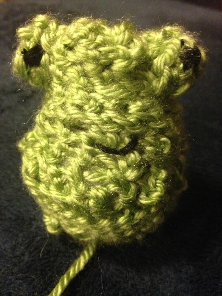 Head of a crocheted frog with embroidered black eyes and smile. Still working on the extra body parts