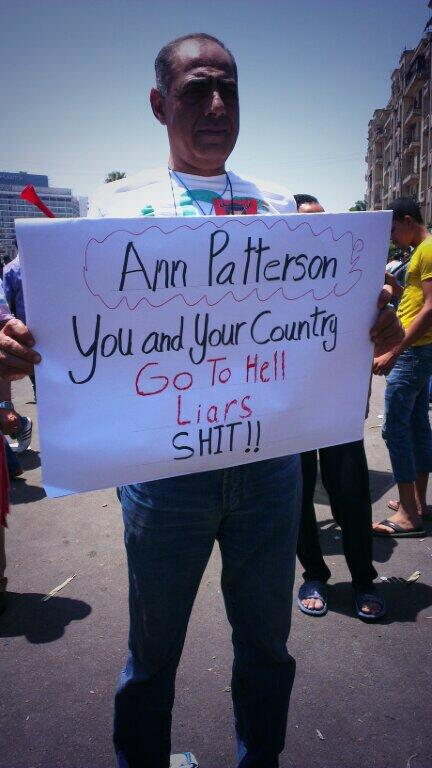 Unidentified man in a Tahrir square holding sign blasting US ambassador to Egypt, Ann Patterson