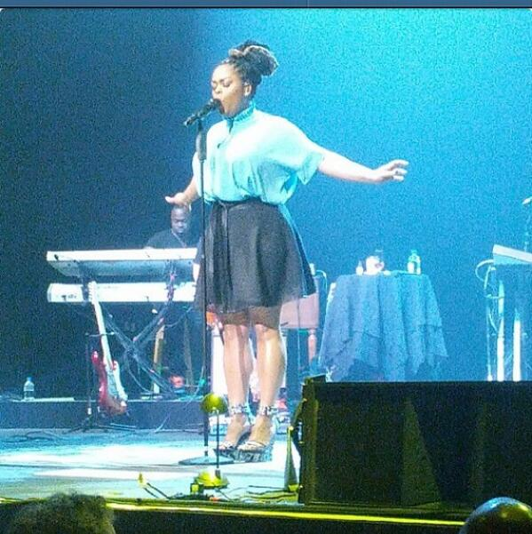 Skinny curvacious Jill Scott performing on stage in blue mini skirt