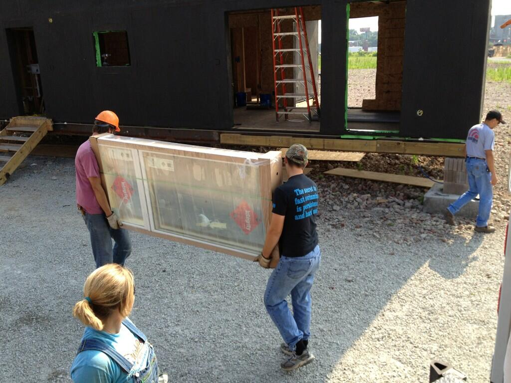 Photo of two Team Kentuckiana students carrying a window for installation.