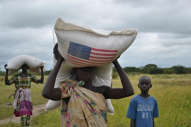 Best flying of a U.S. flag: A woman carries a bag of food in Gumuruk where @WFP is assisting IDPs uprooted by violence.