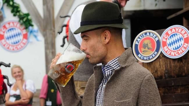 Pep Guardiola enjoying a litre of Paulaner at Oktoberfest, sporting a trilby hat