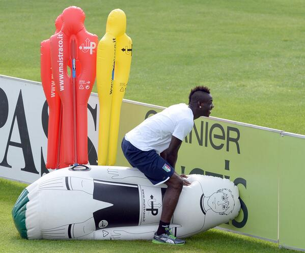 Mario Balotelli clowning around at Italy training, straddles inflatable player