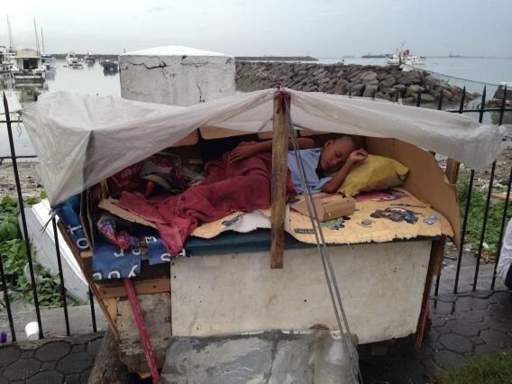 A little boy gets some shelter from rain in Manila. Terrible devastation from Typhoon #haiyan further south. http://t.co/wtMCU3DSRV