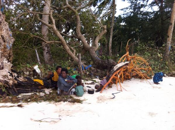An Aeta family beside an uprooted tree at Bulabog Beach, Boracay the morning after typhoon Yolanda struck the island http://t.co/nvTZCAc8RA
