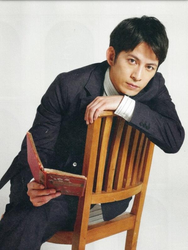 椅子の背もたれに手をかけて本を手にする岡田准一